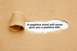 The text A negative mind will never give you a positive life, appearing behind torn brown paper.